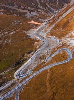 Foto vertical de alto ângulo de uma estrada de asfalto estreita passando por colinas cobertas de grama