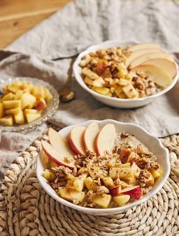 Foto vertical de alto ângulo de uma tigela mingau com cereais, nozes e fatias de maçã em uma mesa