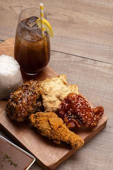 Foto vertical de asas de frango deliciosamente cozidas com molho e gergelim em uma bandeja com uma bebida gelada