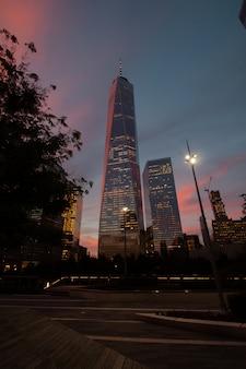 Foto vertical de baixo ângulo de arranha-céus iluminados sob o céu do pôr do sol