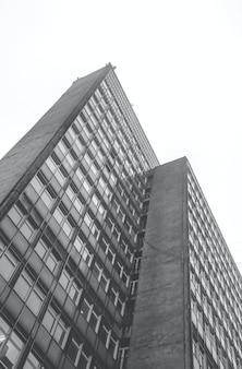 Foto vertical de baixo ângulo em tons de cinza de um edifício residencial durante o dia