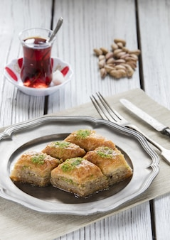 Foto vertical de baklava de sobremesa do ramadã turco em uma mesa de madeira