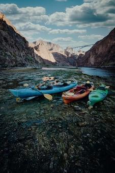 Foto vertical de barcos de caiaque coloridos na margem do lago nas montanhas