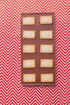 Foto vertical de barra de chocolate com biscoitos retangulares crocantes