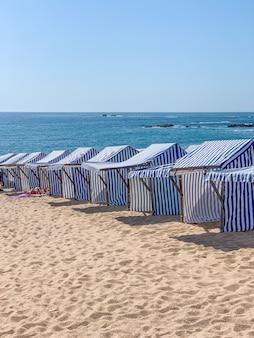 Foto vertical de barracas de praia listradas de azul e branco em portugal