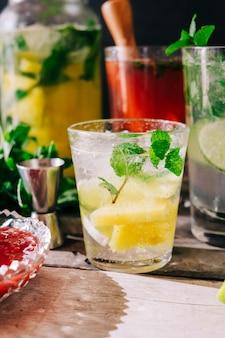 Foto vertical de bebidas frias recém-feitas com frutas e hortelã na mesa
