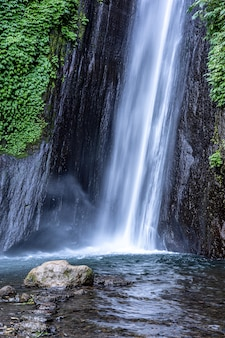 Foto vertical de belas cachoeiras no ar terjun munduk na indonésia gobleg