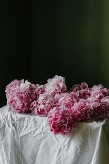 Foto vertical de belas peônias rosa pastel desabrochando em uma mesa