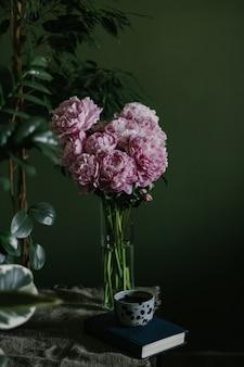 Foto vertical de belas peônias rosa pastel em flor, dispostas em um vaso de vidro