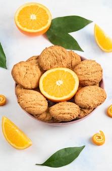 Foto vertical de biscoitos caseiros com meia laranja cortada em uma tigela.