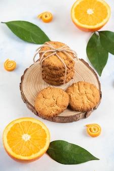 Foto vertical de biscoitos caseiros na placa de madeira e laranjas frescas suculentas.