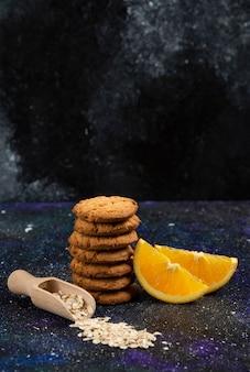 Foto vertical de biscoitos com rodelas de laranja e aveia sobre a mesa escura.