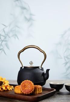 Foto vertical de biscoitos deliciosos e chaleira de chá de ervas