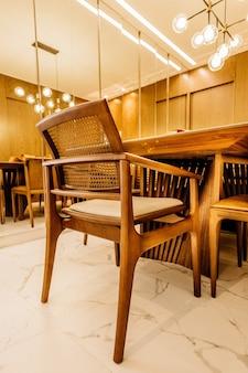 Foto vertical de cadeiras e mesas de madeira em uma sala de estar moderna