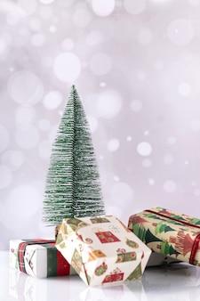 Foto vertical de caixas de presente de natal e uma pequena árvore em bokeh