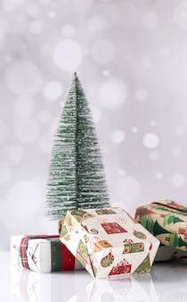 Foto vertical de caixas de presente de natal e uma pequena árvore