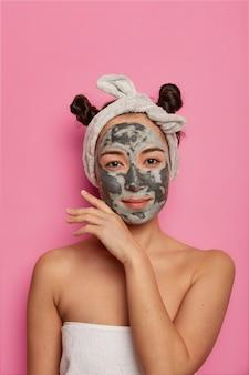 Foto vertical de calma mulher séria tocando sua pele saudável e macia, gosta de rotina de beleza de spa, aplica máscara facial refrescante, usa toalha macia em volta do corpo. é hora de procedimentos de spa, cuidado com a pele