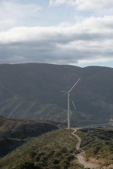 Foto vertical de colinas cobertas de vegetação com um moinho de vento no fundo sob um céu nublado