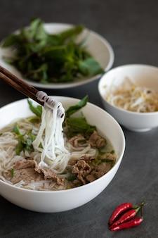 Foto vertical de comida vietnamita, sopa pho bo com pimenta vermelha na mesa