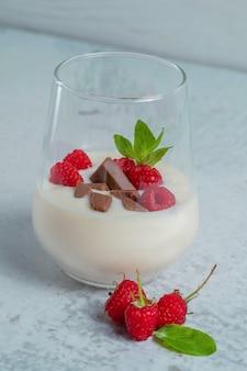 Foto vertical de copo de milkshake de framboesa refrescante.