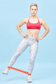 Foto vertical de corpo inteiro de uma jovem loira desportiva em roupas esportivas elegantes, treinando na parede azul com banda de resistência em volta dos tornozelos, segurando as mãos na cintura, levantando a perna para o lado