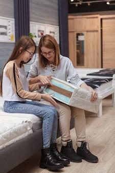 Foto vertical de corpo inteiro de uma mulher madura e sua filha adolescente examinando uma amostra de colchão ortopédico