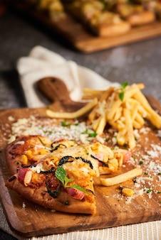Foto vertical de deliciosa pizza servida com batatas fritas em uma placa de madeira