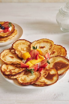 Foto vertical de deliciosas panquecas com frutas em uma mesa de madeira branca