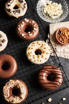Foto vertical de deliciosos donuts cobertos com esmalte de chocolate branco e marrom em uma mesa preta