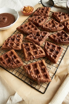 Foto vertical de deliciosos waffles de chocolate em uma rede na mesa perto dos ingredientes