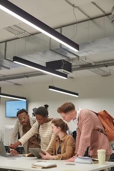 Foto vertical de diversos grupos de alunos trabalhando juntos e usando um tablet digital enquanto estão à mesa no laboratório de ti da escola, copie o espaço
