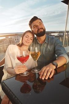 Foto vertical de dois jovens apaixonados se abraçando no pôr do sol, bebendo vinho no terraço do bar