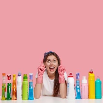 Foto vertical de dona de casa feliz, exclama positivamente, usa luvas de proteção de borracha, aponta para cima para o seu anúncio