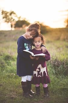 Foto vertical de duas adoráveis irmãzinhas lendo a bíblia no parque