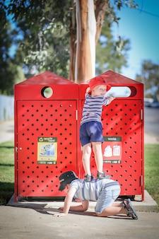 Foto vertical de duas crianças brancas brancas ajudando uma à outra a colocar plástico em uma lixeira
