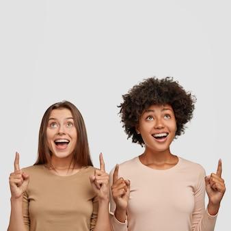 Foto vertical de duas mulheres mestiças espantadas apontando para cima com o dedo indicador