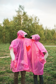 Foto vertical de duas pessoas olhando uma para a outra em fones de ouvido de rv compartilhando uma capa de chuva de plástico rosa