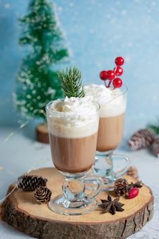Foto vertical de duas taças de sorvete na placa de madeira com decorações de natal.