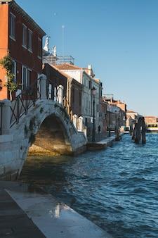 Foto vertical de edifícios e uma ponte sobre a água nos canais de veneza na itália