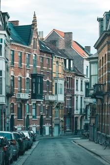 Foto vertical de edifícios residenciais multicoloridos, carros, bicicletas e ruas vazias