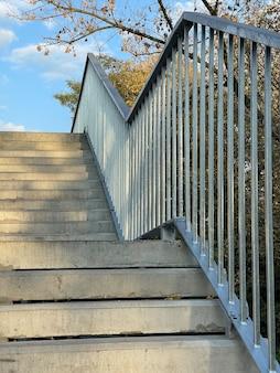 Foto vertical de escadas cinzentas modernas ao ar livre sob o céu azul de outono