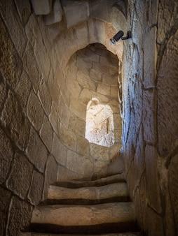 Foto vertical de escadas estreitas dentro de uma torre de pedra com uma pequena janela
