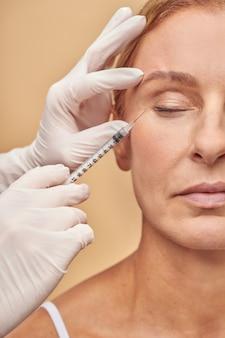 Foto vertical de esteticista com as mãos em luvas de proteção brancas e seringa para fazer injeção cosmética