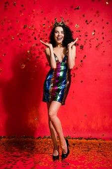Foto vertical de estrelas indicadas para princesa cair usar coroa vestido curto brilhante sapatos de salto alto isolado fundo de cor vermelha brilhante