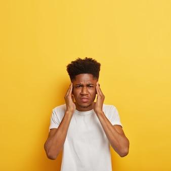 Foto vertical de estudante homem de pele escura insatisfeito mantém as mãos nas têmporas, sofre de uma terrível dor de cabeça