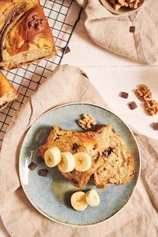 Foto vertical de fatias de delicioso pão de banana com pedaços de chocolate e nozes em um prato