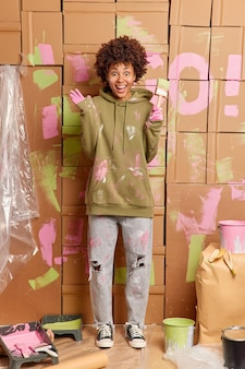 Foto vertical de feliz mulher de pele escura cores paredes do apartamento levanta mãos segura pincel usa moletom sujo e jeans cercado com ferramentas de pintura renova casa após a mudança