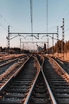 Foto vertical de ferrovias antigas ao pôr do sol