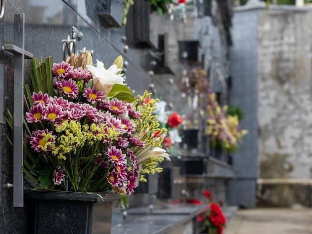 Foto vertical de foco raso de buquês abaixo de lápides de mármore escuro no cemitério
