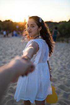 Foto vertical de foco seletivo de uma mulher sorridente de mãos dadas com seu homem
